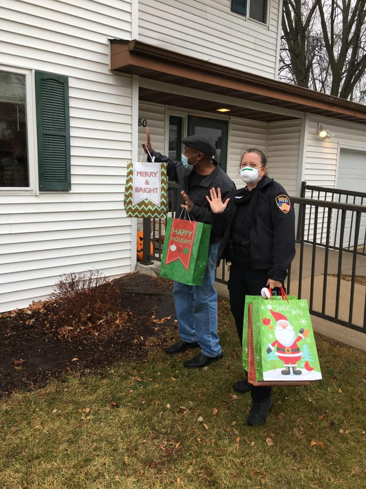 Rodney delivering Christmas gifts with a police officer in Oshkosh